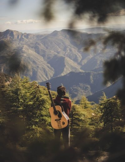 person-with-acoustic-guitar-standing-in-green-field-near-2108813